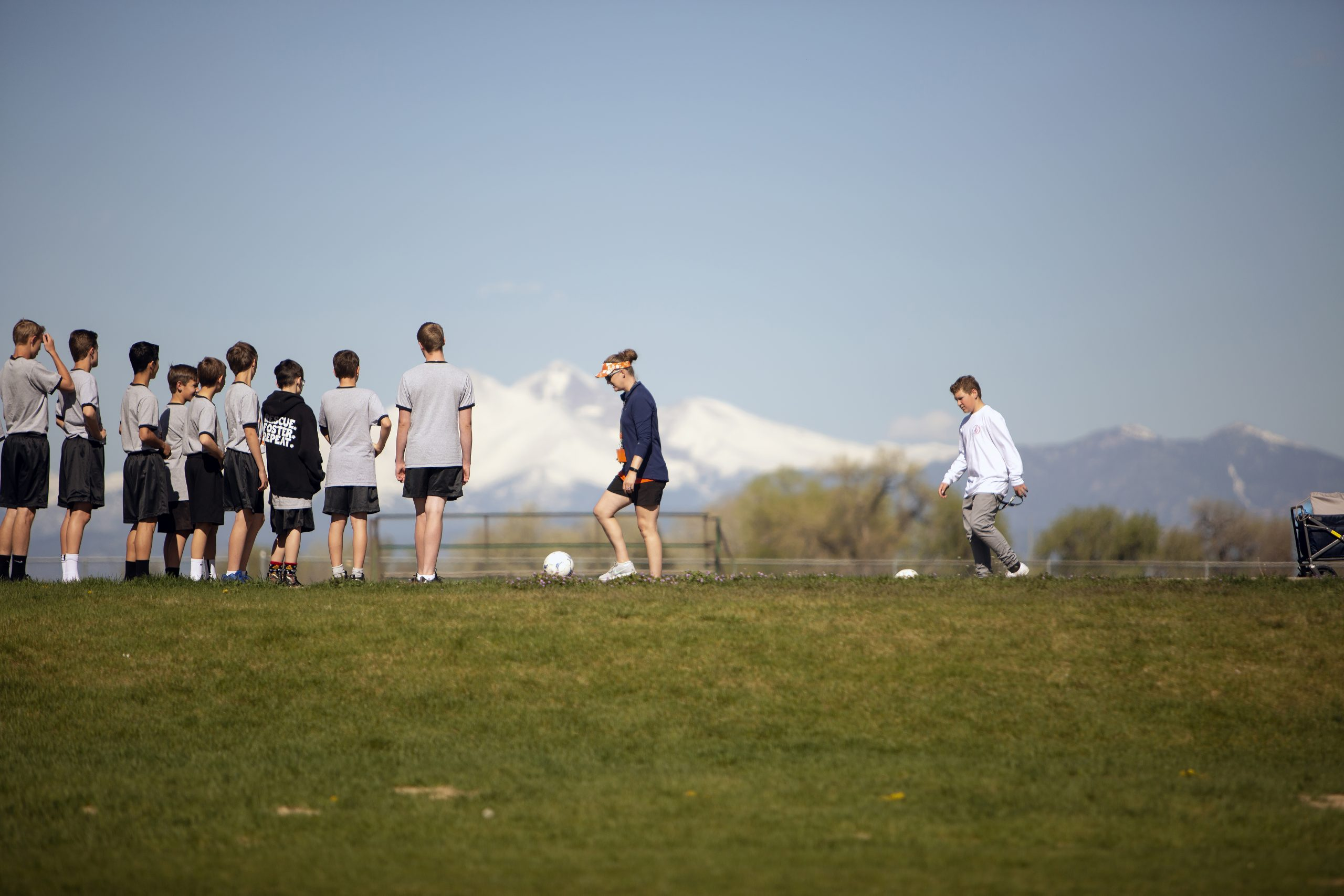 Students playing soccer in front of mountain range
