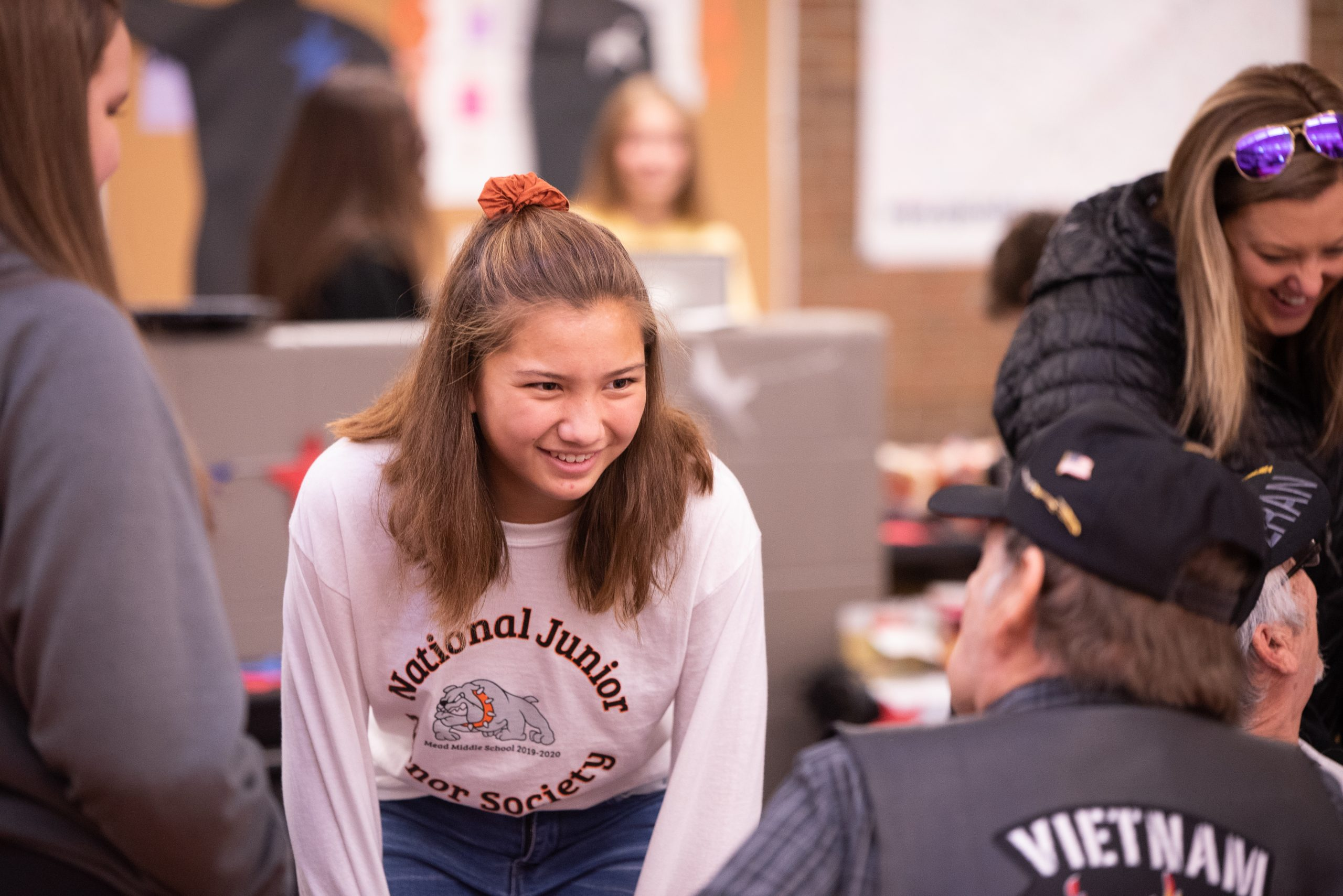 Female student smiling talking to adult